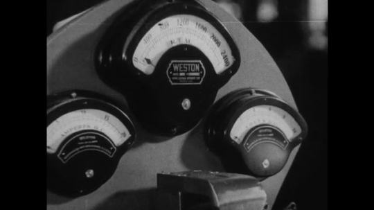 UNITED STATES 1930s-1940s : A close-up of the displays on a car engine part testing machine. A close up shows the electric machine release the engine part on which it was testing.