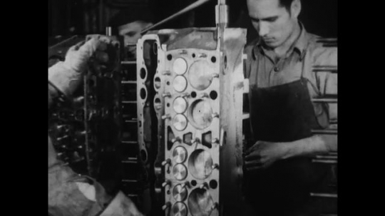 UNITED STATES 1930s-1940s : A factory worker places large metal plates onto engine blocks moving down a conveyor belt. A worker grabs a car part from a track and places it into an engine block.