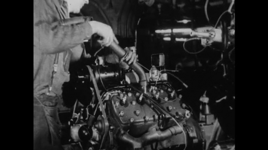 UNITED STATES 1930s-1940s : A factory worker affixes a metal pipe to a v8 engine. An employee observes a machine that tests the v8 engine