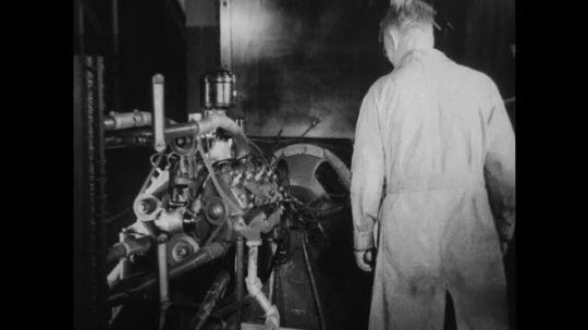 UNITED STATES 1930s-1940s : A factory employee observes a machine that tests a v8 engine