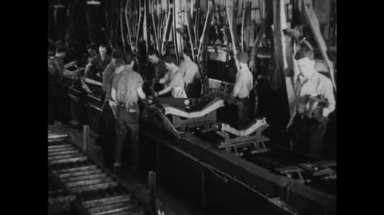UNITED STATES 1930s-1940s : factory workers move finished steel car frame pieces onto a conveyor belt. Two workers move a steel frame part from one machine to another.