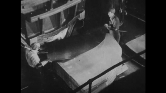 UNITED STATES 1930s-1940s : Two factory workers place a steel sheet onto a press that shapes it into the form of a car exterior.