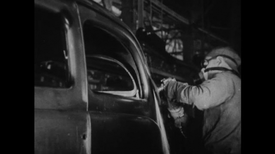 UNITED STATES 1930s-1940s : A factory worker uses a power sander to sand the steel exterior of a partially built car. Other workers buffer a partially built car