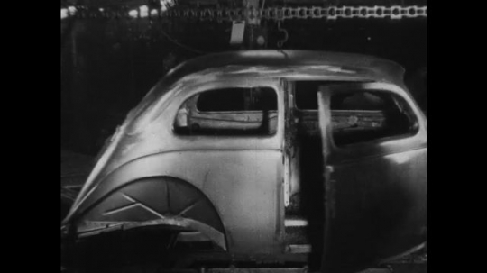 UNITED STATES 1930s-1940s : A factory worker spray paints a fully constructed steel car exterior.