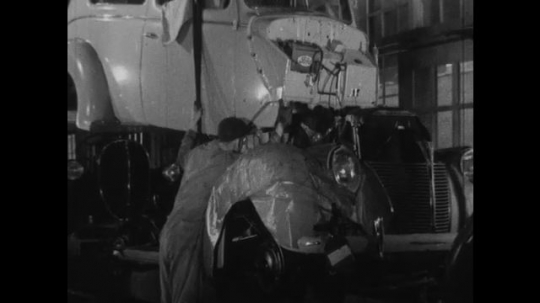 UNITED STATES 1930s-1940s : factory workers lower a steel car exterior onto a car frame and engine. One worker places a tire onto the car. He then places a hubcap on it.