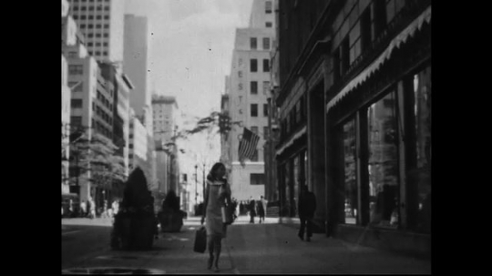 AMERICA: 1950s: A woman carrying a shopping bag and box, walks down an urban street lined with tall buildings. She stops to peer into a shop window before continuing on.