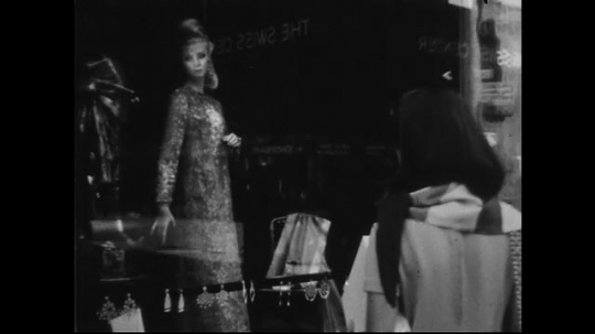 AMERICA: 1950s: A woman approaches a glass display window at a store and looks at a mannequin in a dress.