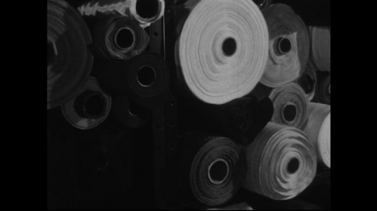 AMERICA: 1950s: Various shots of fabric rolls.  A hand removes one of the fabric rolls from a large stack.
