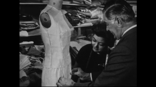AMERICA: 1950s: A man in a suit helps two female dress makers as they tailor their dresses on mannequins.