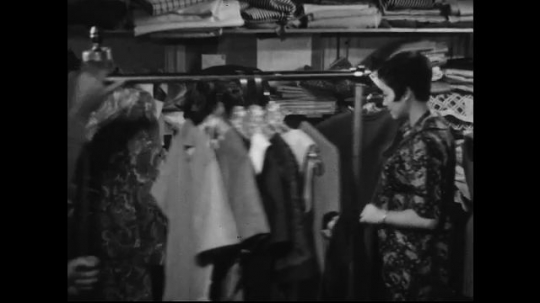 AMERICA: 1950s: Two women in a tailor's shop admire a finished dress. An older man in a suit takes a call in an office.  A younger man comes by to show him a piece of paper.