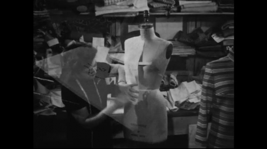 AMERICA: 1950s: A dressmaker begins to make a seam by folding and pinning a piece of fabric on a mannequin.