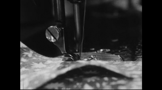 AMERICA: 1950s: A woman uses a sewing machine to stitch a seem into a piece of fabric.