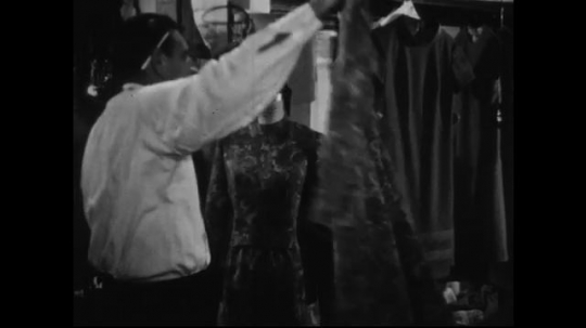 AMERICA: 1950s: A tailor places a dress onto a mannequin and checks it to ensure that it has no defaults.