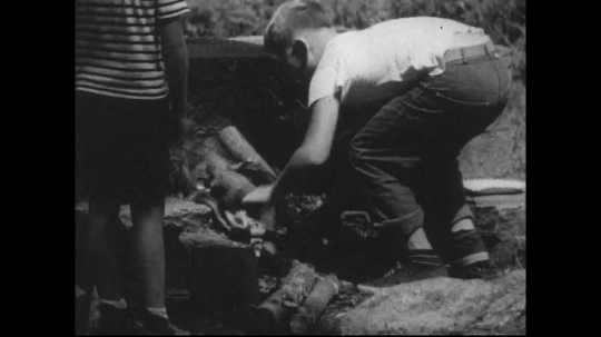 UNITED STATES 1940s: Boys pulls wood off fire, fans with paper plate / Close up, hand fans flame / Brother watches boy tend fire / Hand fans flame.