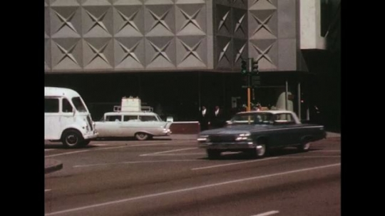 UNITED STATES 1960s: Cars driving and eventually enter a lot.