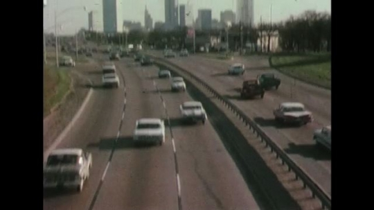 UNITED STATES 1960s: Cars driving into and out of Dallas-Fort Worth with a signal tower in sight.