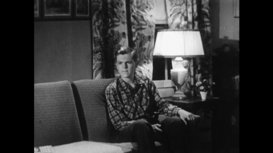 UNITED STATES 1950s: A young man pondering while sitting on his couch as another discusses his concerns over food.