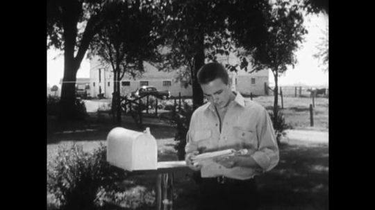 UNITED STATES 1950s: A man looks at his mail while teenagers talk about important issues while eating in a restaurant.