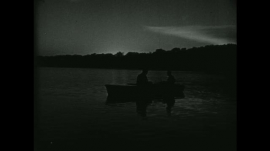 UNITED STATES 1950s: Two men row a boat at dawn.