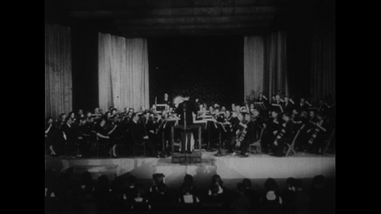 UNITED STATES CIRCA 1951 : An orchestra plays to the beat of the conductor during a concert.