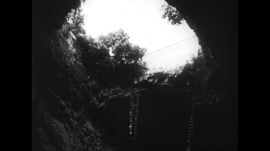 UNITED STATES CIRCA 1951 : Ropes hang from a widened hole in a sparsely-populated area in Italy.