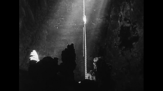 UNITED STATES CIRCA 1951 : A man climbs down a rope into the White Grotto  through a hole.