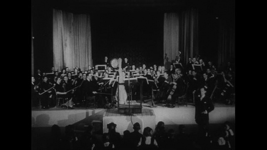 AUSTRALIA CIRCA 1951 : Professor Bernard Heinze takes the podium for a lesson on symphonic orchestra in front of a group of young students.