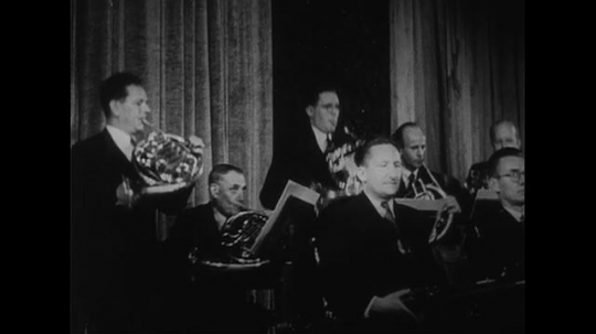 AUSTRALIA CIRCA 1951 : French horn players in an orchestra stand up and play a tune.