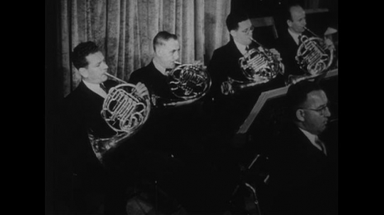 AUSTRALIA CIRCA 1951 : French horn players play a tune in an orchestra.
