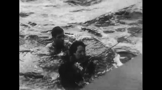 UNITED STATES CIRCA 1951 : After a helicopter crash in the sea, three passengers are rescued by the Navy and change into dry clothes.