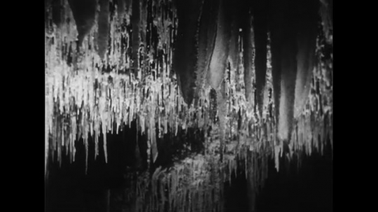UNITED STATES CIRCA 1951 : Stalactites hang from the ceilings as stalagmites build up from the floor of the White Grotto cavern in Italy.