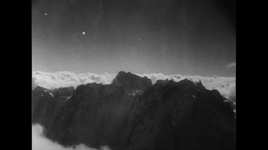 SWITZERLAND CIRCA 1951 : Two men discuss landing plans as they fly through Mont Blanc in Switzerland.