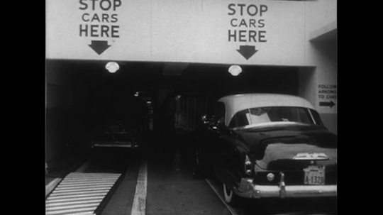 UNITED STATES CIRCA 1951 : A customer leaves her car to an attendant at a parking garage.