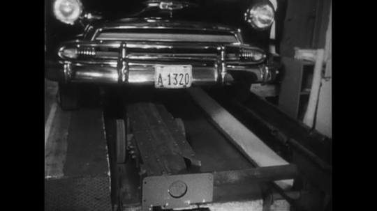 UNITED STATES CIRCA 1951 : A car is loaded into an elevator in a parking garage through the control of an attendant.