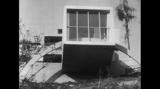 HOLLYWOOD CIRCA 1951 : A Hollywood hillside house is supported by a flood arch as it sits atop a steep area.