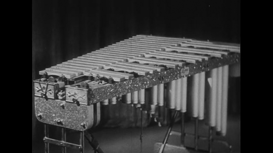 AUSTRALIA CIRCA 1951 : Professor Bernard Heinze continues with his list of percussion instruments as some are struck.