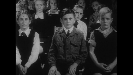 AUSTRALIA CIRCA 1951 : Students eagerly listen as percussion instruments are struck by musicians.