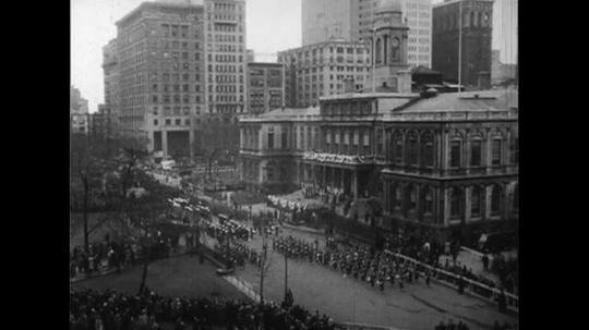 UNITED STATES 1950s: High angle view of parade, New York street / Vincent Auriol kisses Mayor Impellitteri / Wider view, Press surrounding Auriol and Impellitteri.