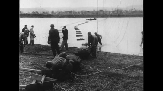 UNITED STATES 1950s: Troops construct bridge across river / Officer talks to Dwight Eisenhower / Troops construct bridge.