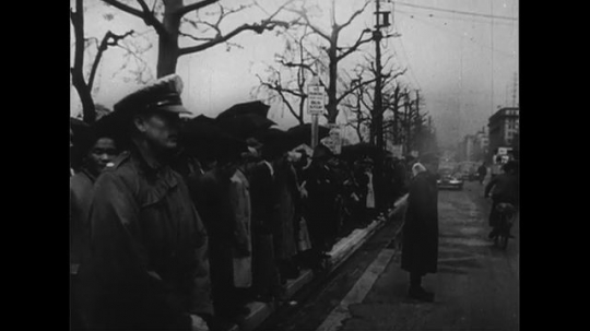 UNITED STATES 1950s: Crowd on sidewalk in Tokyo / Car pulls up to camera / Douglas MacArthur exits car / MacArthur walks past crowd into building.