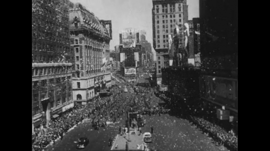 UNITED STATES 1950s: Long shot of parade on New York City street / Man throws ticker tape out window / People wave from windows / Douglas MacArthur in car / Low angle shot of buildings, ticker tape.