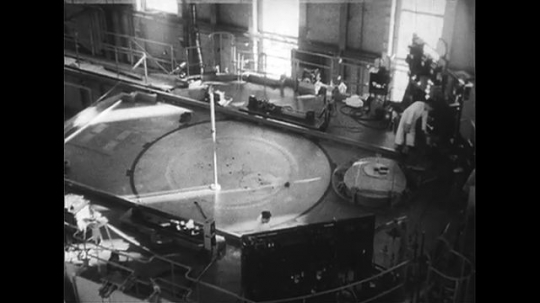UNITED STATES 1950s: High angle views of men working on top of nuclear reactor / Safety warning sign in plant.