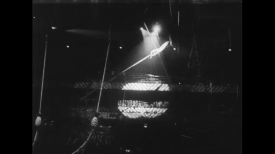 UNITED STATES 1950s: Man balancing on pole, pole swings to ground / Woman on trapeze / View of audience.