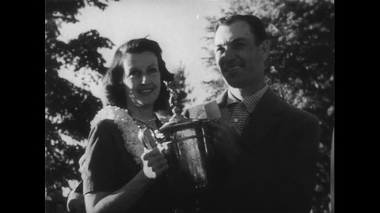 UNITED STATES 1950s: Ben Hogan with wife, holds trophy / Hogan tees off / Long shot of crowd / Panning shot of Hogan hitting ball onto green.