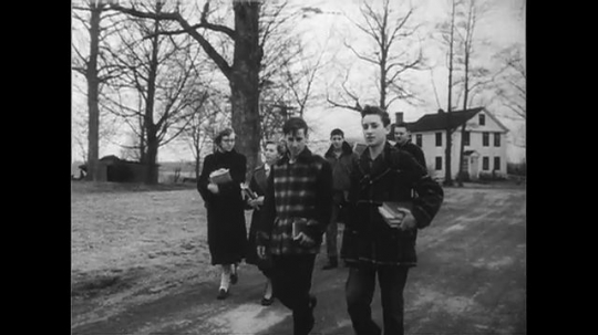 UNITED STATES 1950s: Panning shot of teenagers walking on road / Students walking toward school / Students in shop class.