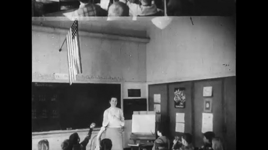 UNITED STATES 1950s: Teacher and students in classroom, students raise hands / United Nations flag / Students walk into classroom.