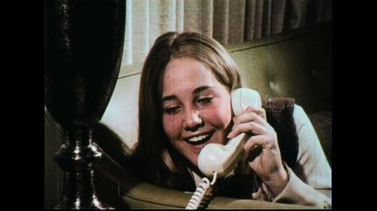 UNITED STATES 1970s: A girl smiles as she talks on the phone.