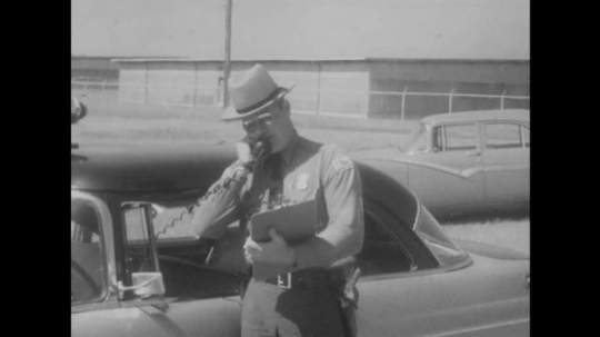 Police Man Holds Clipboard and Makes Call on Car Radio.