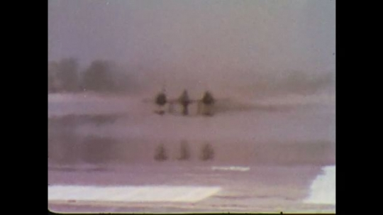 UNITED STATES: 1960s: Heat vapours on runway as plane takes off. US Airforce plane on ground. Operations building