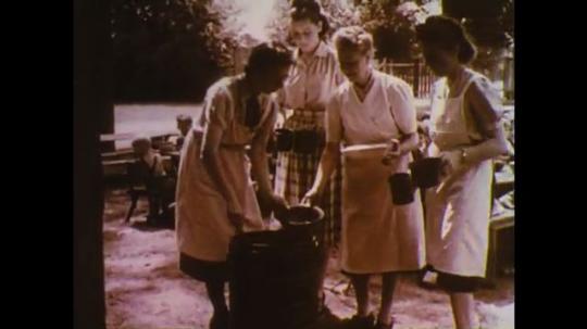 UNITED STATES: 1960s: Ladies serve food to children. Children eat food at table. Girl eats from bowl. Boy eats food from bowl. Military planes take off.